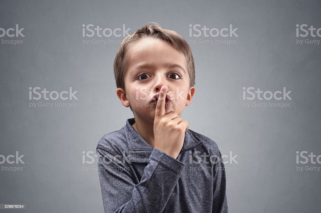Shh boy with finger on lips stock photo