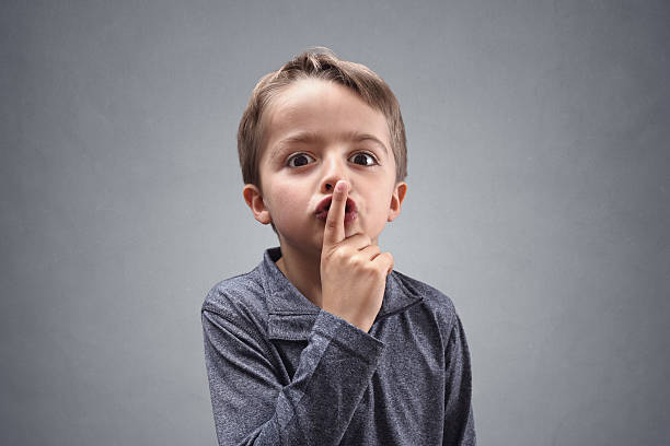 Shh boy with finger on lips Boy with finger on lips making a silent shhh gesture finger on lips stock pictures, royalty-free photos & images