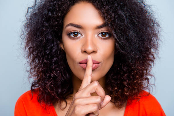Shh! Closeup portrait of mysterious charming woman with modern hairdo asking for keeping silence holding forefinger on plump lips isolated on grey background stock photo