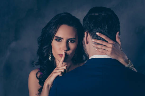 Shh! Portrait of tempting brunette lady showing silence sign with forefinger touching secret mysterious gentlemen with rear view, lovely Mr and Mrs isolated on grey background stock photo