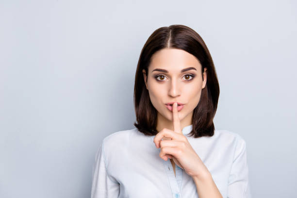 Shh shy sly people person modern concept. Close up portrait of cute lovely attractive uncertain unsure with stylish hairdo entrepreneur making hush gesture isolated on gray background copy-space stock photo