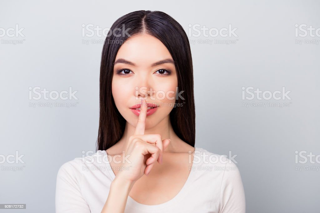 Shhh! Close up portrait of  young woman with  finger showing hush silence sign, cute girl asking for silence, standing over grey background Shhh! Close up portrait of  young woman with  finger showing hush silence sign, cute girl asking for silence, standing over grey background Adult Stock Photo