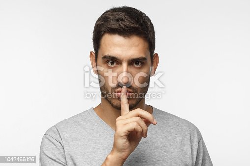 Shhh gesture. Young man isolated on gray background dressed in white casual t-shirt pressing finger to lips as if asking to keep silenc
