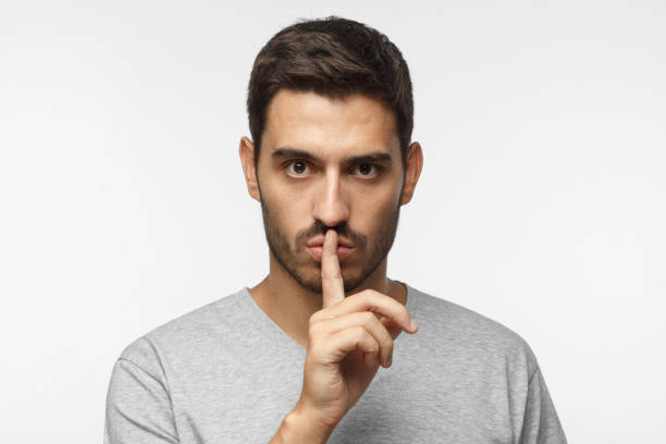 Shhh gesture. Young man isolated on gray background dressed in white casual t-shirt pressing finger to lips as if asking to keep silenc Shhh gesture. Young man isolated on gray background dressed in white casual t-shirt pressing finger to lips as if asking to keep silenc finger on lips stock pictures, royalty-free photos & images