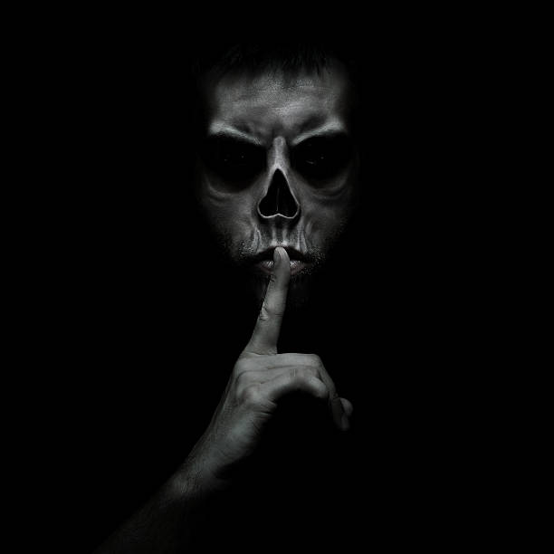 Shhh Evil man gesturing silence, quiet isolated on black background human skull stock pictures, royalty-free photos & images