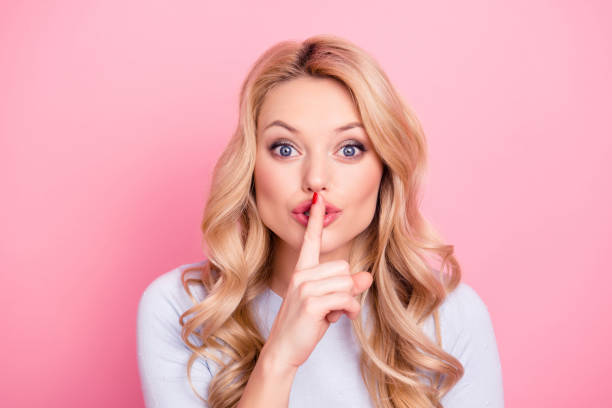 Shhh! Portrait of pretty mysterious girl in casual outfit showing silence sign holding forefinger on lips having curly hair modern hairdo isolated on pink background Shhh! Portrait of pretty mysterious girl in casual outfit showing silence sign holding forefinger on lips having curly hair modern hairdo isolated on pink background finger on lips stock pictures, royalty-free photos & images