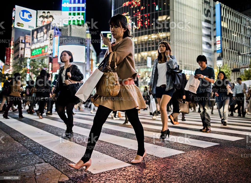 People walking at Shibuya crossing at night in Tokyo. Shibuya is one...