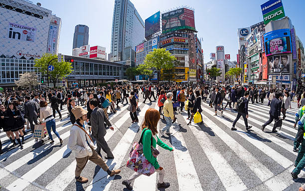 Shibuya Crossing A wide angle view of Tokyo Japan's Shibuya Crossing on a work day. All signs and logos are visible. middle of the road stock pictures, royalty-free photos & images