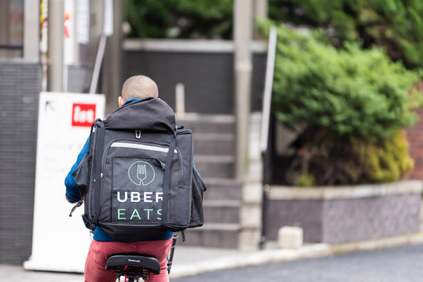Shibuya street road with back of young delivery man on bicycle for uber eats stock photo