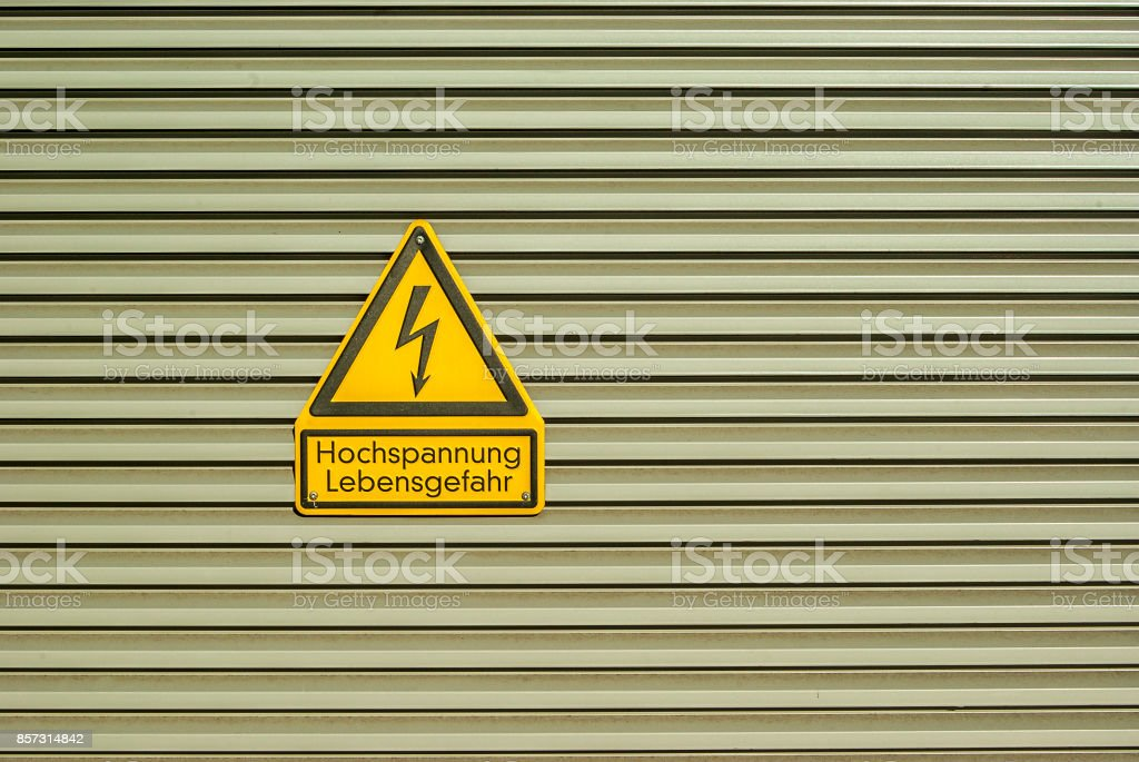 Shield Attention High voltage Danger to life on metal door with crosswise metal lamellas stock photo