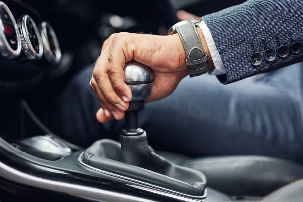 Shifting gears Cropped shot of an unrecognizable man's hand on his gearstick while driving gearshift stock pictures, royalty-free photos & images