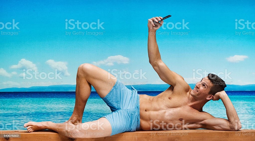 Shiftless muscular man taking a selfie in the beach stock photo