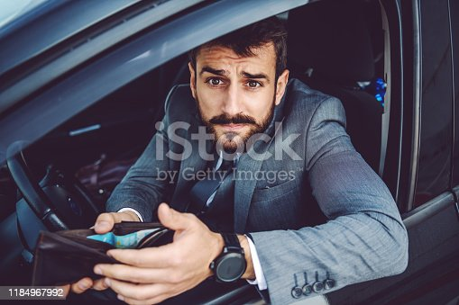 istock Shifty caucasian businessman sitting in his car and trying to bribe police officer. 1184967992