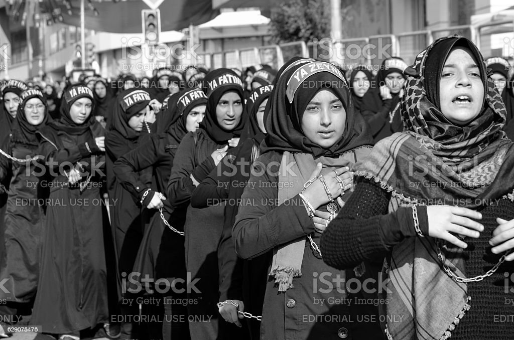 Shiite Muslim women hold up their chained hands. stock photo