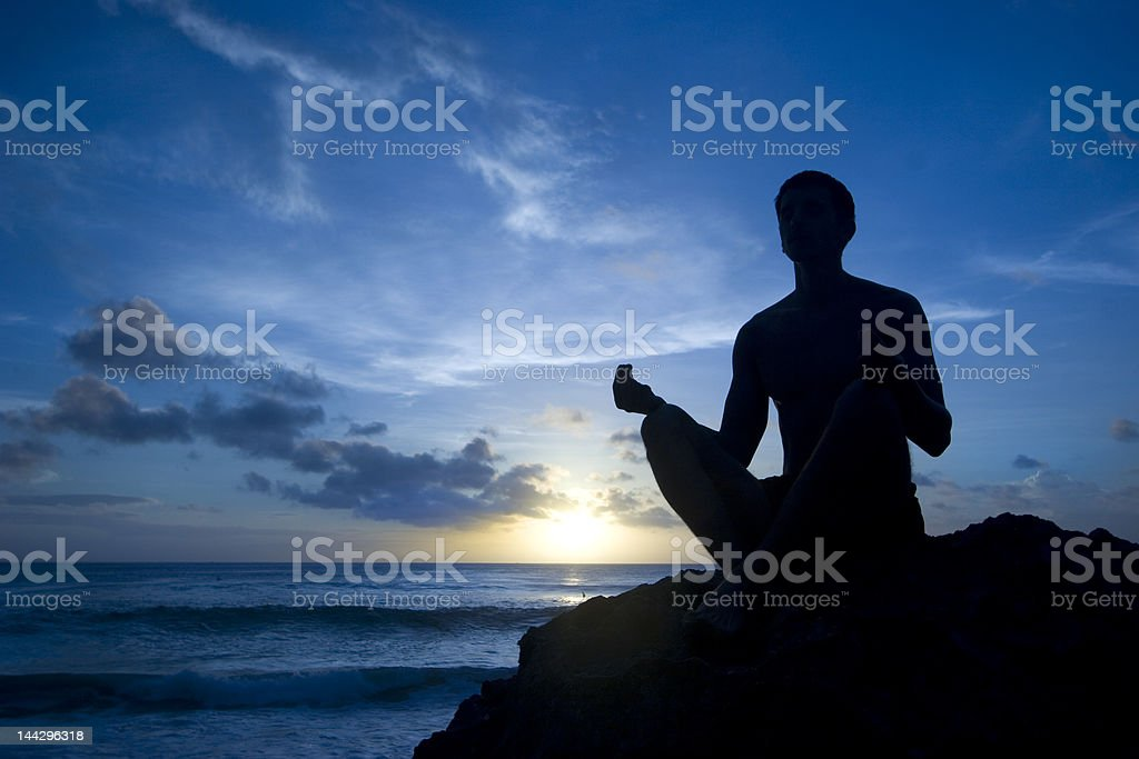 Shilouette of man meditating on the beach royalty-free stock photo