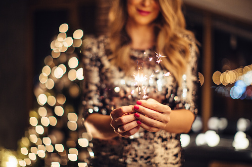 Close up of woman's heands holding sparklers. Woman wearing sparkly elegant dress. Evening or night.
