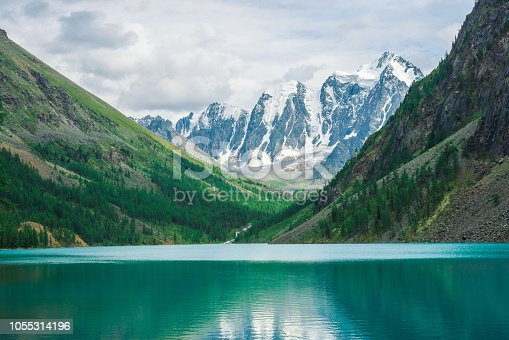 istock Shine water in mountain lake in highlands. Wonderful giant snowy mountains. Creek flows from glacier. White clear snow on ridge. Amazing atmospheric landscape of majestic Altai nature. 1055314196