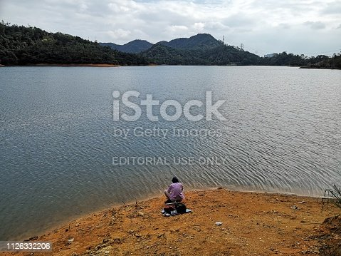 Man on the shore o the idyllic Shing Mun reservoir Country Park, located in New Territories of Hong Kong.