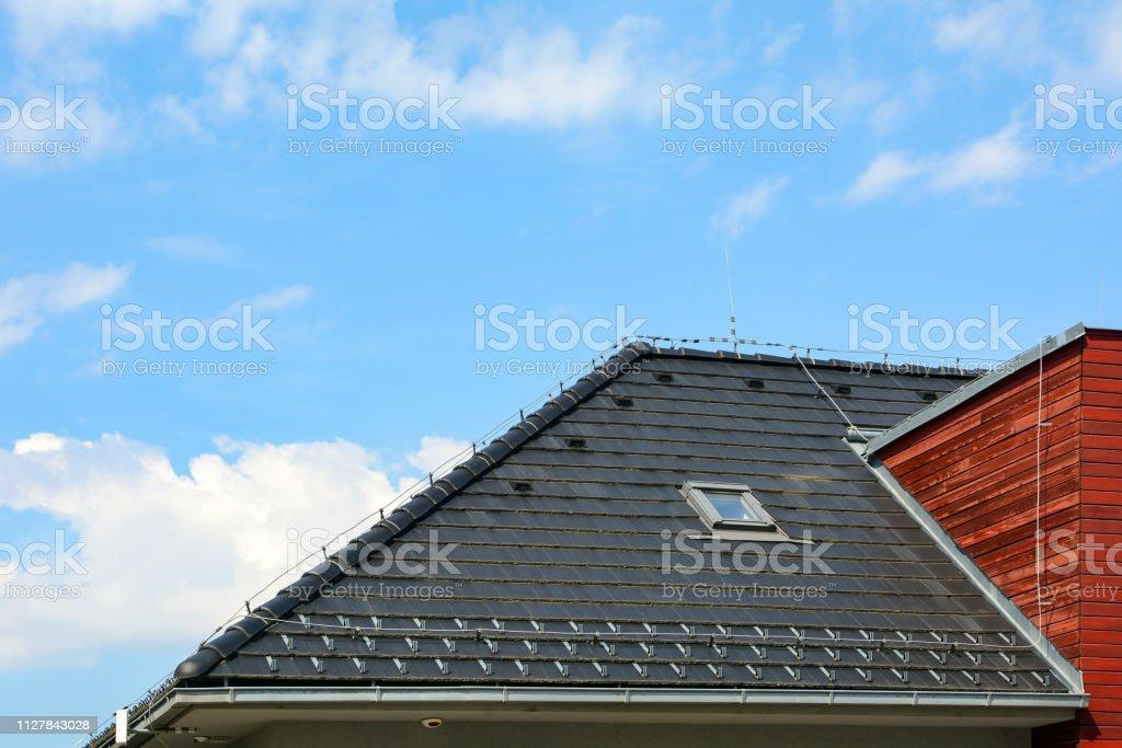 Schindeln Dach mit Oberlichtern Windows und Regenrinne auf dem Hintergrund des blauen Himmels. Backstein-Haus mit Blitzableiter. – Foto