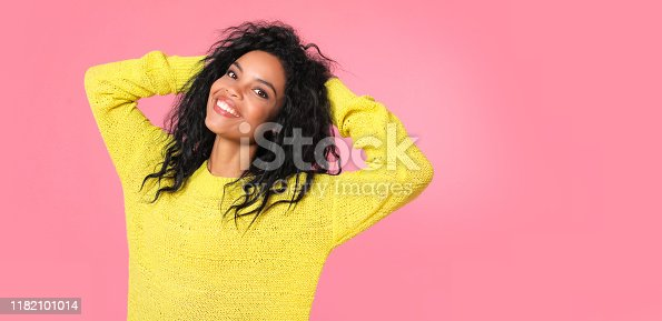 857924506 istock photo Shining brightly. African ethnic woman with jet-black wavy hair in yellow knitted sweatshirt is posing with her hands over her head, looking at the camera and smiling with joy. 1182101014