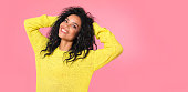 istock Shining brightly. African ethnic woman with jet-black wavy hair in yellow knitted sweatshirt is posing with her hands over her head, looking at the camera and smiling with joy. 1182101014