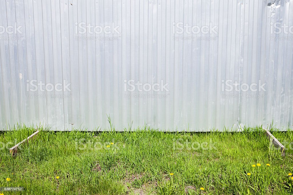 Shining Corrugated Metal Fence On Green Grass Stock Photo