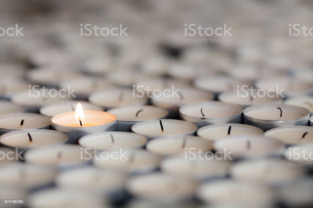 Shining light from a solitary burning candle flame. Selective focus on one tealight among many. stock photo