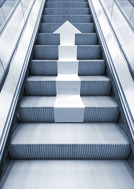 Shining metal escalator with white arrow moving up stock photo