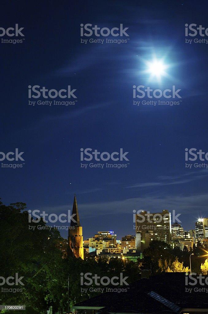 Shining moon, church, city lights stock photo