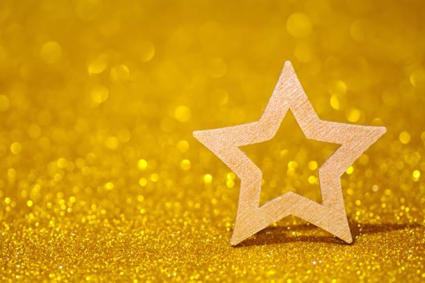 leuchtender stern auf einem goldenen leuchtenden hintergrund. glitter-glanz mit stern - promi schmuck stock-fotos und bilder
