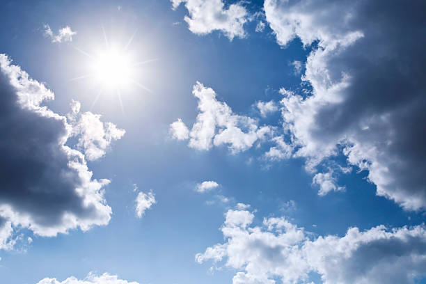 Shining Sun framed by clouds on a blue sky stock photo