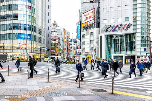 Tokyo, Japan - March 28, 2019: Shinjuku crosswalk with traffic of crowd many people crossing street in morning rush hour commute on road near pachinko building