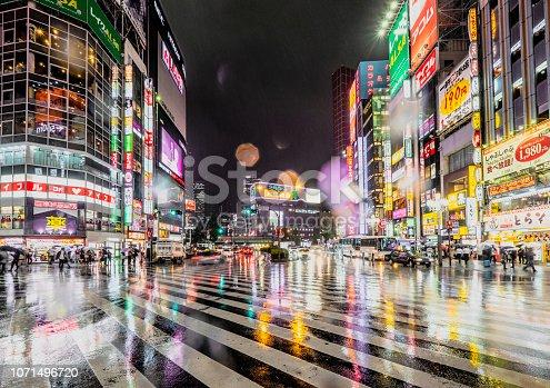 A crowded street at night in Shinjuku, Tokyo, Japan.