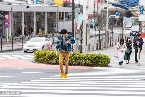 Tokyo, Japan - March 30, 2019: Shinjuku street sidewalk with people man crossing road pavement walking by buildings during day