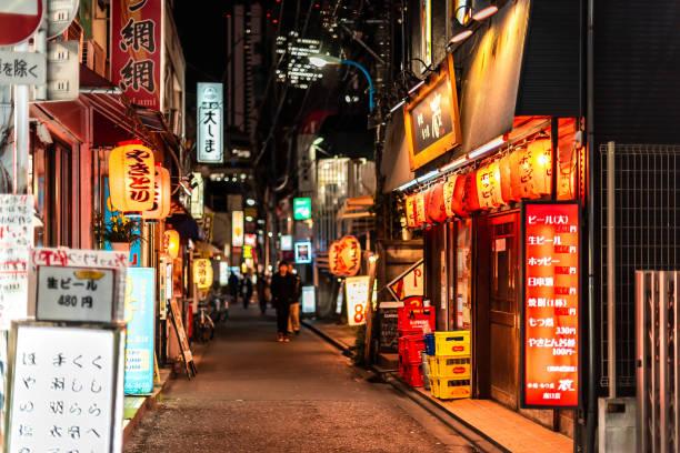 Shinjuku ward downtown street with izakaya restaurants at night and signs near Okubo station stock photo
