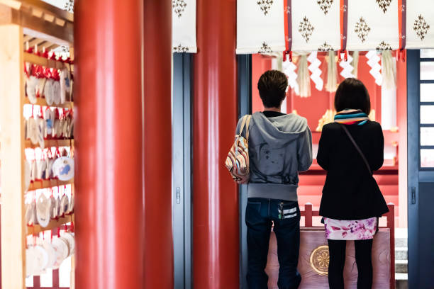 Shinto temple near Hie shrine entrance and young couple Tokyo, Japan - March 31, 2018: Shinto temple near Hie shrine entrance withback of young couple praying at altar inside shrine stock pictures, royalty-free photos & images