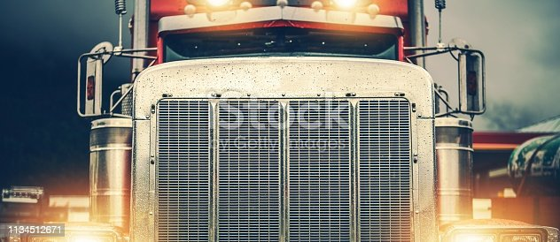 Shiny American Semi Truck on a Road. Large Chromed Grill Front View in Wide Format. Trucker on the Road.