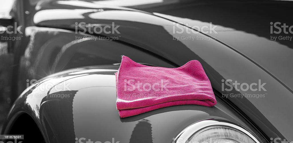 Shiny and clean black car with a pink rag on top stock photo