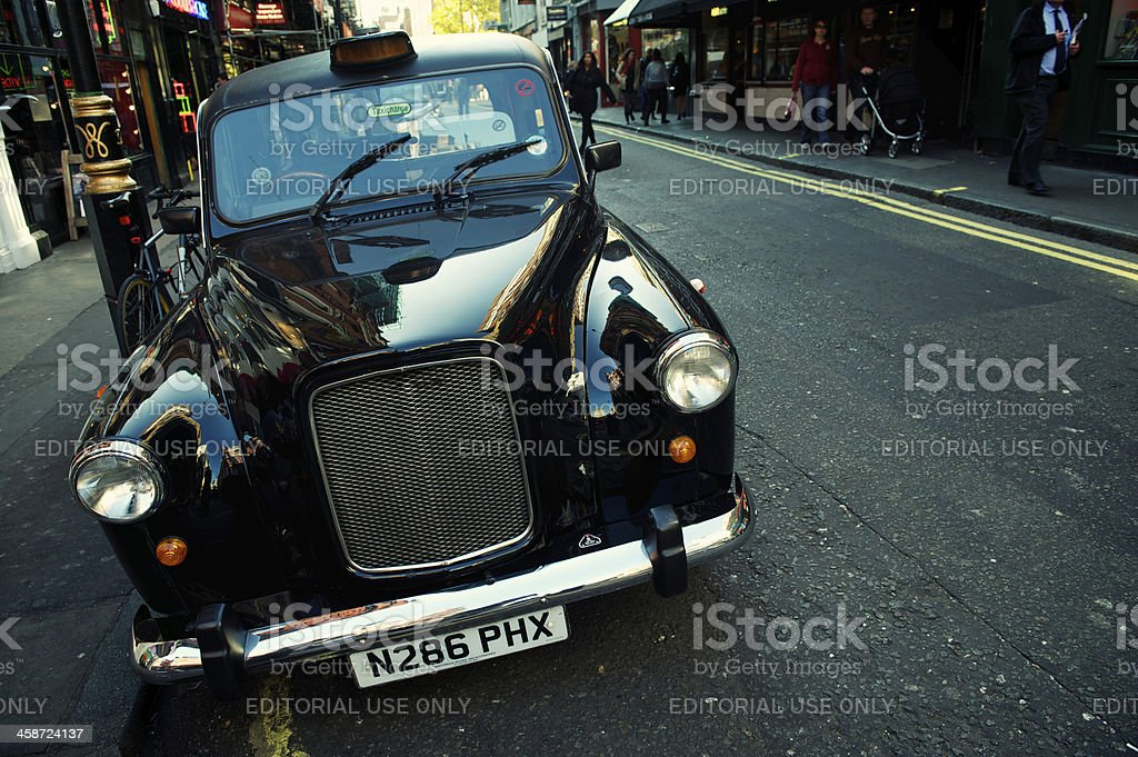 Shiny Black Cab Stands Parked on London Street stock photo
