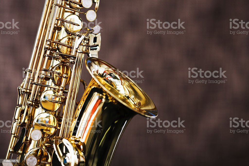 Shiny bright saxophone in close up against brown background royalty-free stock photo