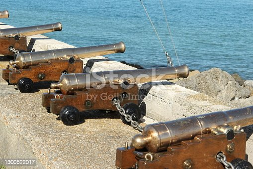 A row of shiny cannons pointing out to sea