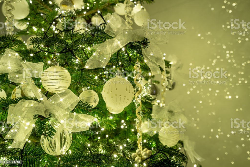 A shiny christmas decoration is hanging on a christmas tree stock photo