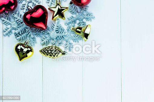 istock Shiny Christmas holiday ornaments on white wood background 622964392