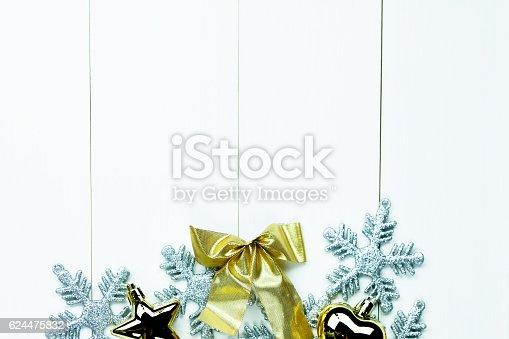 istock Shiny Christmas holiday ornaments on white wood background 624475832