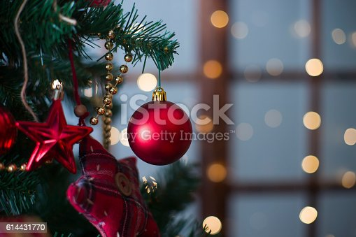 istock Shiny Christmas red ball hanging on pine branches 614431770