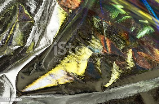 1053870408istockphoto Shiny crumpled surface of silver foil with gold reflects for textured background. 1158199599