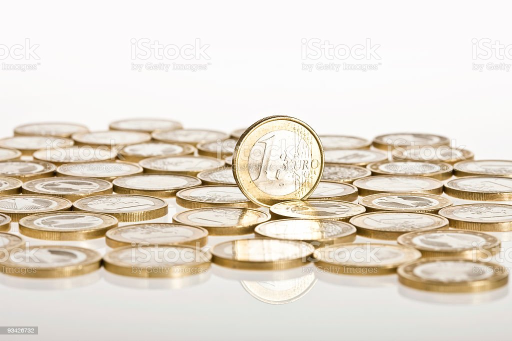 Shiny euros lay on the white surface while one stands royalty-free stock photo