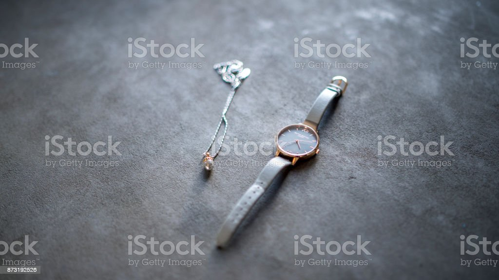 Shiny Female Watch and Acorn Necklace With Flowers in Vase on Scandinavian Grey Table