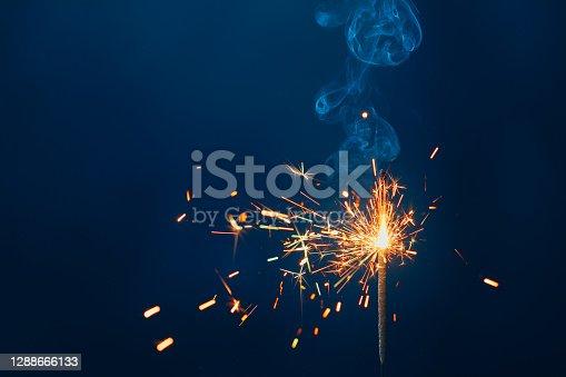 istock shiny fire sparkler on dark blue background 1288666133