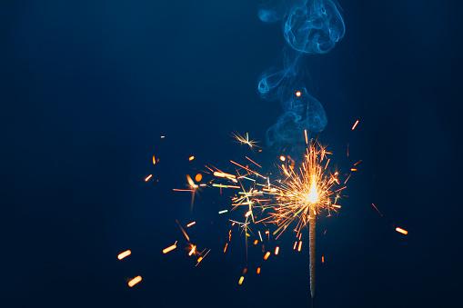 shiny fire sparkler on dark blue background